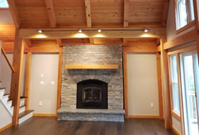 Custom living area with stone fireplace by G & L Contrating.
